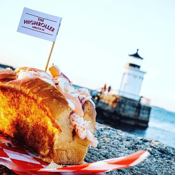 Lobster roll on grilled hot dog bun with a Highroller Loberster Co flag and Bug Light Lighthouse in the background