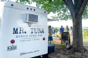 Mr Tuna Mobile Sushi Bar food truck with patrons ordering looking on the Eastern Prom of Portland, Maine